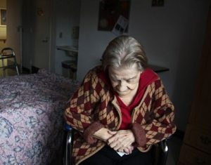 Cariati Law Toronto, Ontario Injury Lawyers Nursing Home Abuse Elderly Woman looking sad in dark room alone