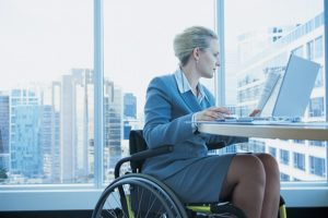 Cariati Law Toronto, Ontario Injury Lawyers Long Term Disability Lawyers Woman in Wheelchair working on laptop in Office