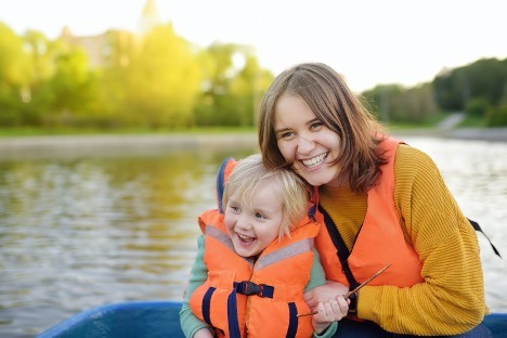 Mother and son practicing safe boating on a lake