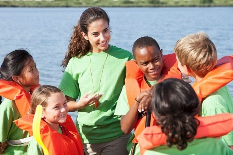 Young woman educating group of children on safe boating procedures