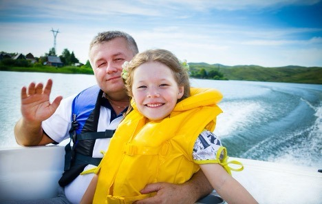 Father and daughter smiling on boat wearing life jackets