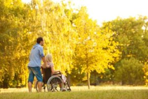 Man pushing woman in wheelchair through a park with Long Term Disability