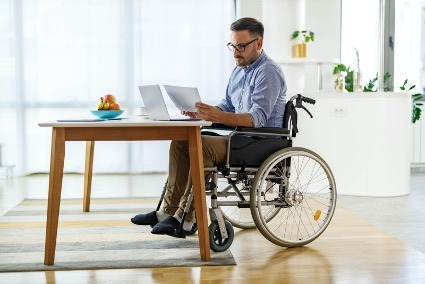 Man on wheelchair reading long term disability papers